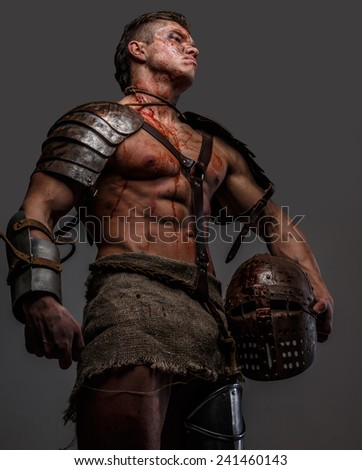 Wounded gladiator standing and holding his helmet - stock photo