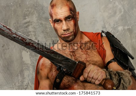 Wounded gladiator with  sword covered in blood isolated on grey - stock photo