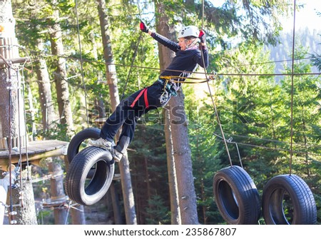woung woman  hanging on tires in an adventure park in the forest - stock photo