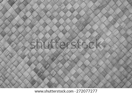 Woven bamboo mat with geometrical cross patterns in black, white, and gray tones. - stock photo