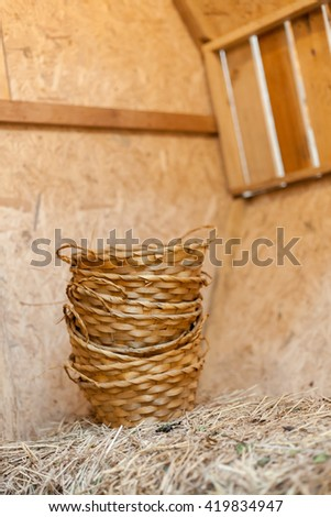 Woven basket placed on a pile of hay in the barn. - stock photo