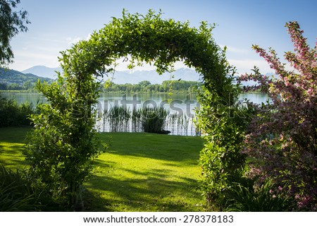 Woven plants forming an arch in beautiful garden by the lake, surrounded by flowers - stock photo