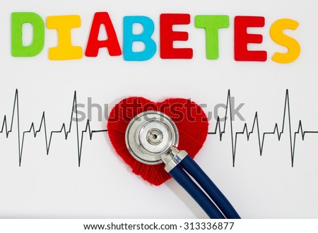 Woven red heart and the stethoscope on the cardiogram. Diabetes - stock photo