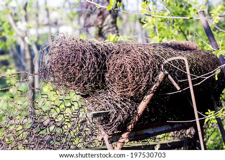 Woven rusty wire for fences on a metallic prop with natural background - stock photo