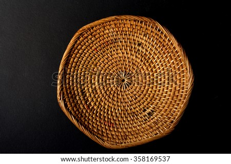 woven tray - woven using natural ingredient on black background - stock photo