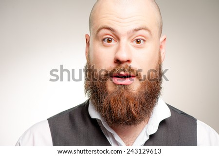 Wow! Surprised young caucasian bearded man in white shirt staring at camera while standing against gray background - stock photo