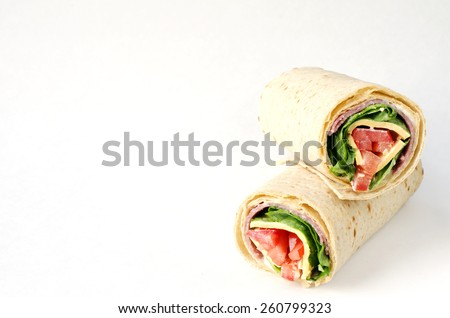 wrap sandwich with salami, lettuce, tomatoes and cheeses on white background with copy space. - stock photo