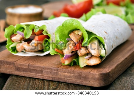 Wrap sandwiches with chicken meat and fresh vegetables, close up view - stock photo