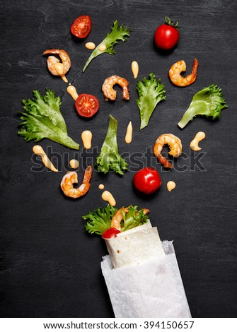 wrap with prawn, tomatoes and lettuce ib paper bag. Top view - stock photo