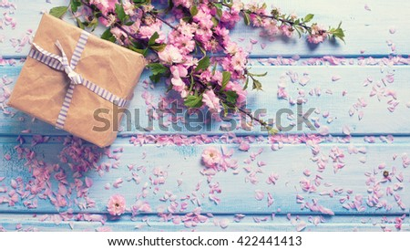 Wrapped box with present and sakura pink flowers on blue wooden planks. Selective focus. Place for text. Flat lay. Top view. Toned image. - stock photo