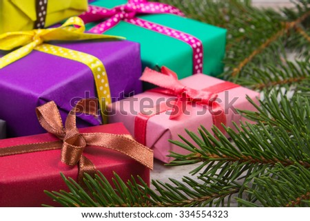Wrapped colorful gifts for Christmas, birthday or other celebration and green spruce branches on old white wooden plank - stock photo