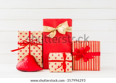 Wrapped gifts boxes and red heart on white wooden background. Copy space  - stock photo