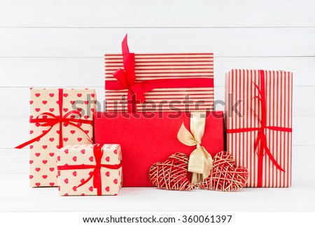Wrapped gifts boxes and two red hearts on white wooden background. Copy space  - stock photo