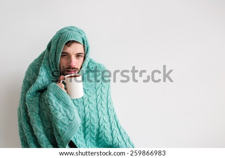 wrapped in the warm turquoise knitted blanket, sick, bearded man with a red nose snotty drinking warm healing tea  - stock photo