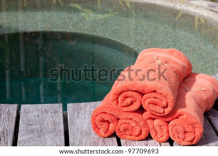 wrapped orange towels by the private pool - stock photo
