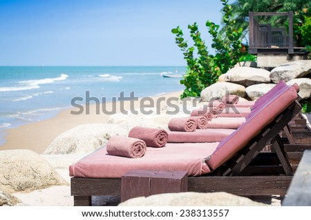 wrapped towels with empty sunbed on a beautiful beach - stock photo