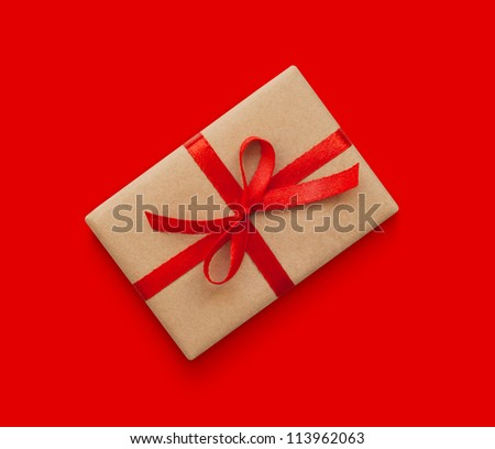 Wrapped vintage gift box with red ribbon bow, isolated on red - stock photo