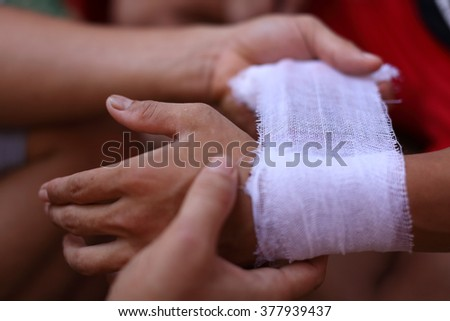 Wrapping the hands of a traditional Burmese kickboxer (Lethwei) in gauze in Hpa An, Myanmar (Burma) - stock photo