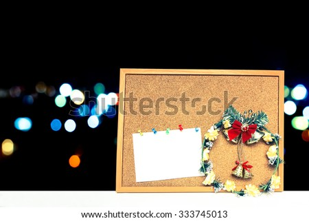 Wreath and card on cork board with  blur bokeh light in city background - stock photo