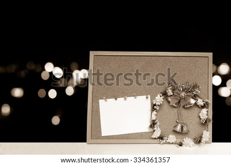 Wreath and card on cork board with  blur bokeh light in city background ,vintage tone - stock photo