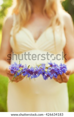 wreath from cornflowers in the hands - stock photo