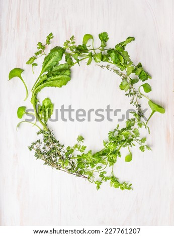wreath of green herbs: thyme, coriander, parsley, mustard, marjoram , oregano, chervil , Cuminum , watercress , savory on white wooden background, top view - stock photo