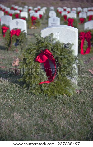 Wreaths placed at a national military cemetery as part of a Wreaths Across America event - stock photo