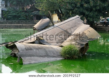 Wreckage of an American B-52 bomber in Huu Tiep Lake, Hanoi, Vietnam. Shot down by Vietnamese SAM during Operation Linebacker II in 1972. The wreckage is left where it crashed and now a War Memorial. - stock photo