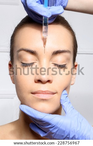 Wrinkle reduction, the lion's wrinkle injection Botox.Portrait of a white woman during surgery filling facial wrinkles  - stock photo