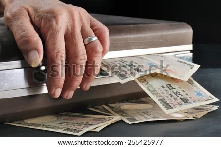 wrinkle senior hand touch suitcase full of Yen cash in dark room, Concept of saving for retirement - stock photo