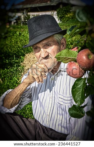 Wrinkled and expressive old farmer leaning on an apple tree in the yard. - stock photo
