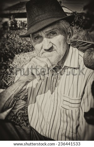 Wrinkled and expressive old farmer leaning on an apple tree in the yard. Sepia picture. Close-up. - stock photo
