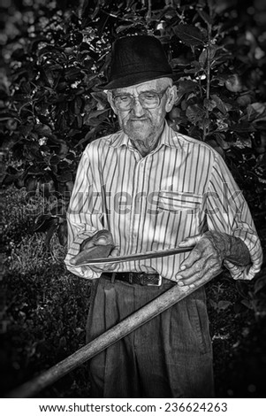 Wrinkled and expressive old farmer sharpening his scythe with an apple tree in the background. Black and white picture. - stock photo