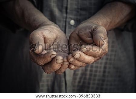 Wrinkled old hands begging asking for money. Closeup portrait senior elderly wrinkled hands isolated dark black background. Human emotions attitude reaction, body language. Charity Concept sign symbol - stock photo
