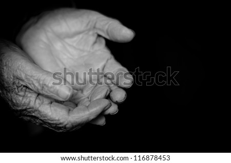 Wrinkled old hands begging isolated on a black background - stock photo