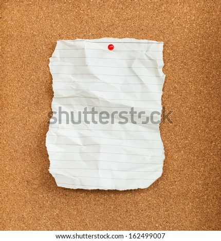 Wrinkled paper with red pin on cork board  - stock photo