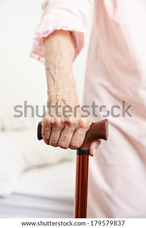 Wrinkly hand of senior woman with walking cane - stock photo