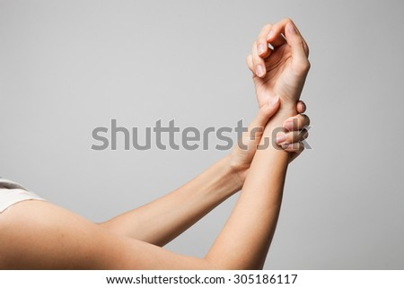 Wrist injury woman holds a hand on her pain wrist. Medical Concept - stock photo