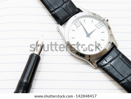 wrist watch and an ink pen on a paper - stock photo