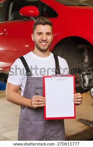 Write Your Text On a Clipboard. Smiling auto mechanic standing against red car on a lift in workshop and holding a clipboard with blank white paper sheet. - stock photo