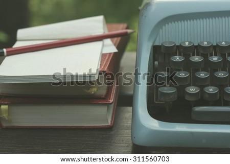 writer's tools. old blue typewriter detail, pile of books, noteb - stock photo