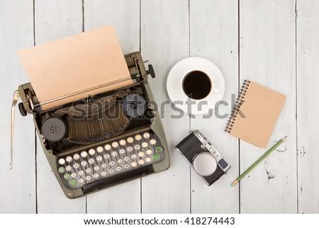 writer's workplace - wooden desk with vintage typewriter  and other supplies - stock photo