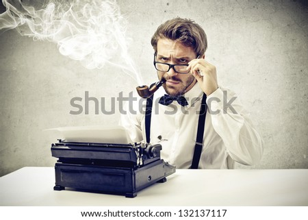 writer smokes a pipe and writes with typewriter - stock photo