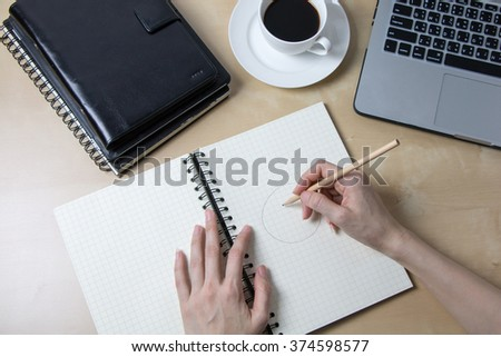 Writing and drawing on working desk with coffee laptop glasses book notepad supplies and tablet  - stock photo
