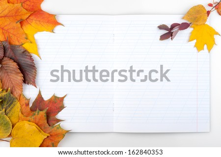 Writing-book and autumn leaves. Concept for Back to school - stock photo