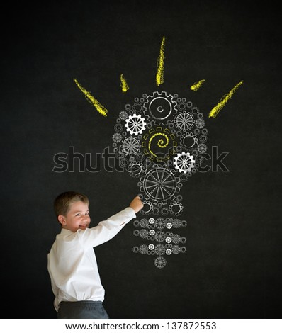 Writing boy dressed up as business man with bright idea gear cog lightbulb on blackboard background - stock photo