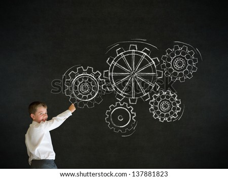 Writing boy dressed up as business man with chalk turning gear cogs or gears on blackboard background - stock photo