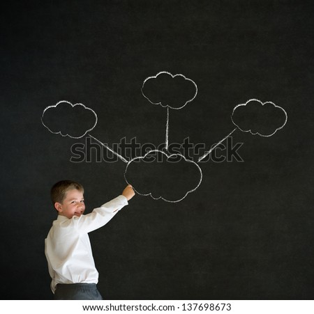 Writing boy dressed up as business man with strategy thought chalk clouds on blackboard background - stock photo