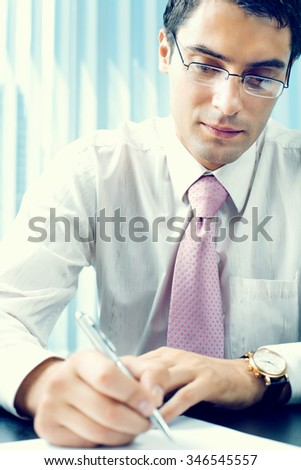 Writing businessman with documents at office - stock photo
