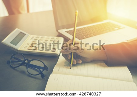 writing,female hands with pen writing on notebook,business women hand working with new modern computer and writing on the notepad strategy diagram ,business concept,vintage color,selective focus - stock photo